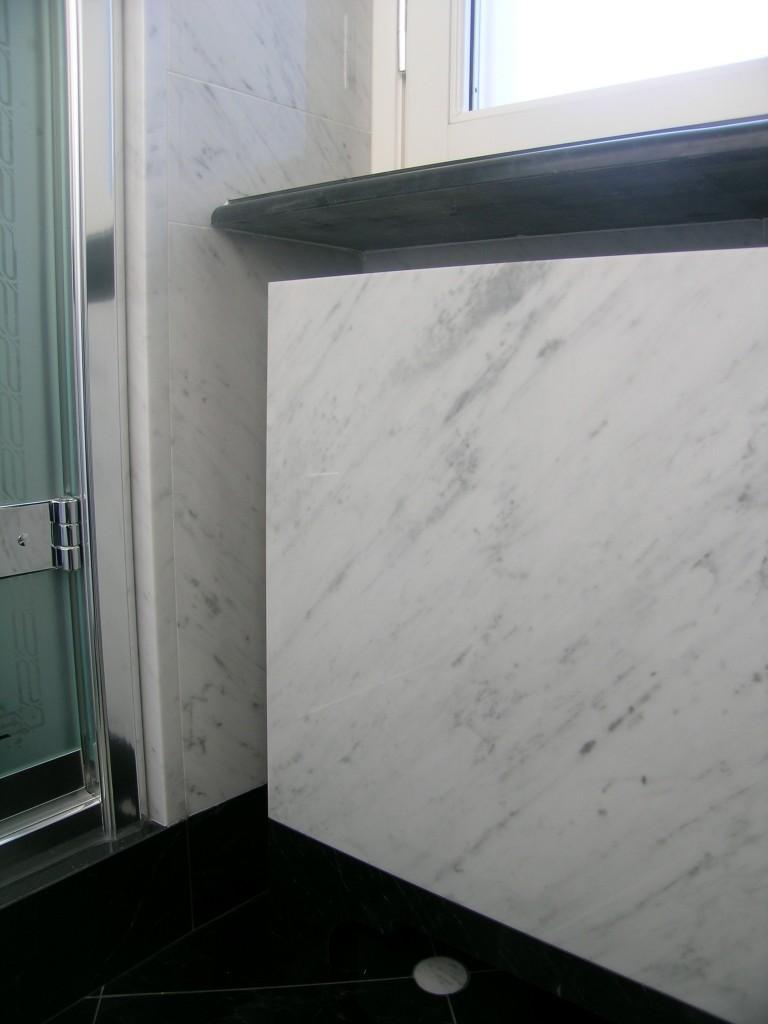 Rivestimento a parete e copritermosifone in marmo bianco di Carrara Pavimento in marmo nero Piemonte